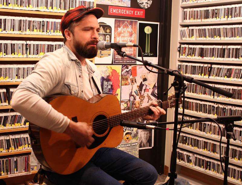 Man sitting on a stool playing guitar and singing into a microphone