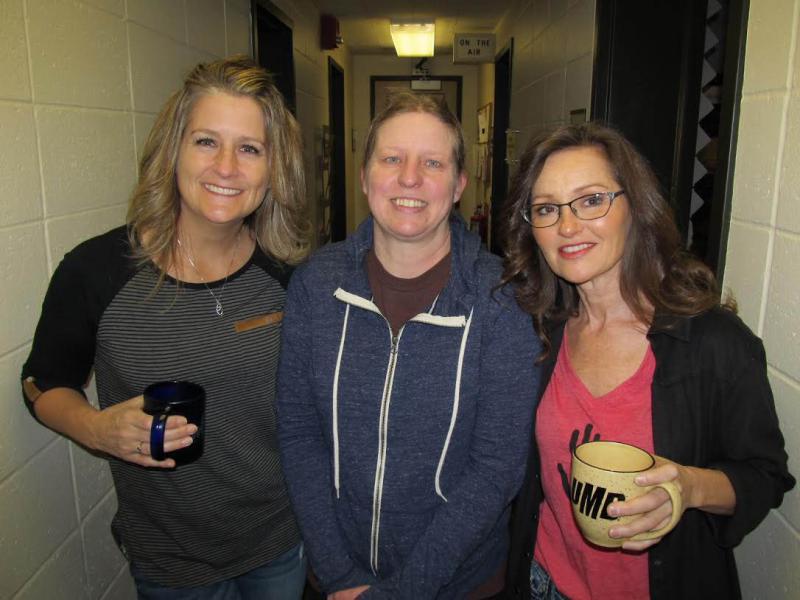 Three women standing in a hallway