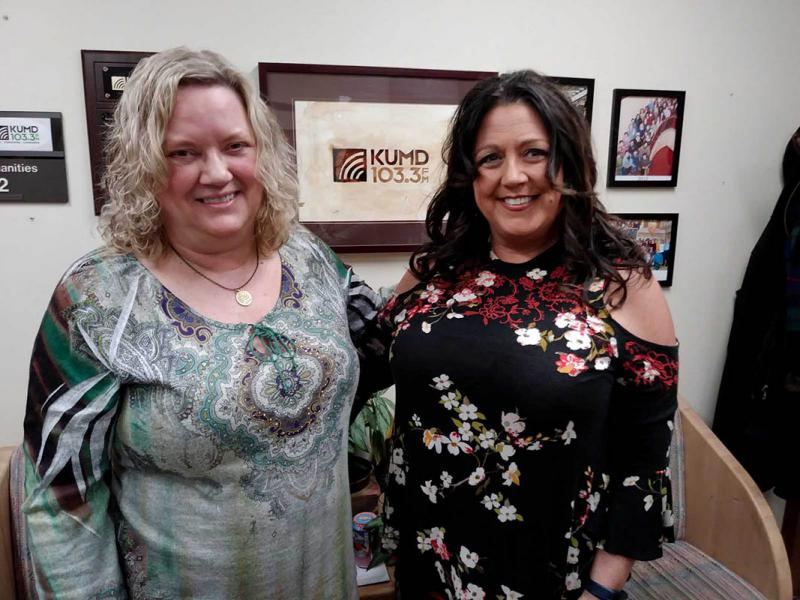 Two women standing in front of a KUMD picture
