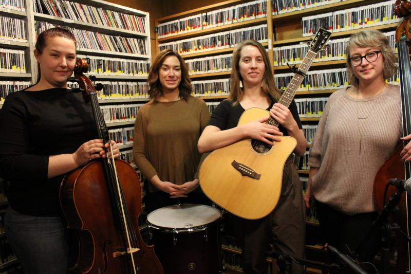 Four women standing with instruments in front of a wall of CDs