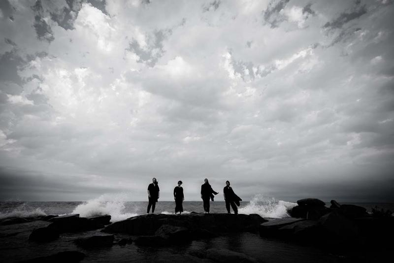Four women standing in front of Lake Superior under a cloudy sky