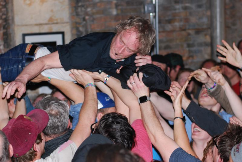 Man crowd surfs with a guitar pick in his mouth