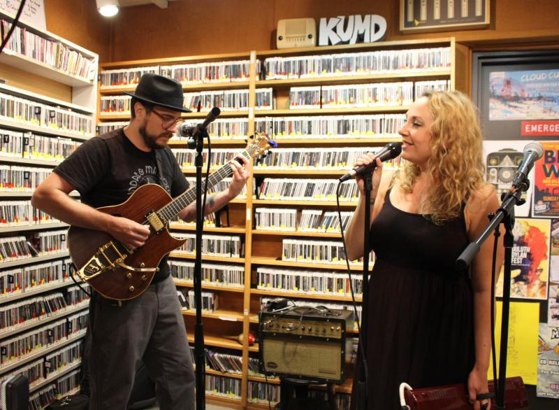 Man playing guitar and woman singing into a microphone in radio studio