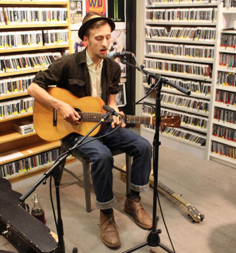 Man in a hat sitting on a stool playing guitar in a radio studio