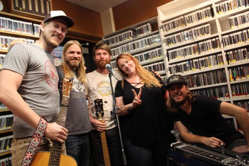 Band standing in front of wall of CDs in a radio studio