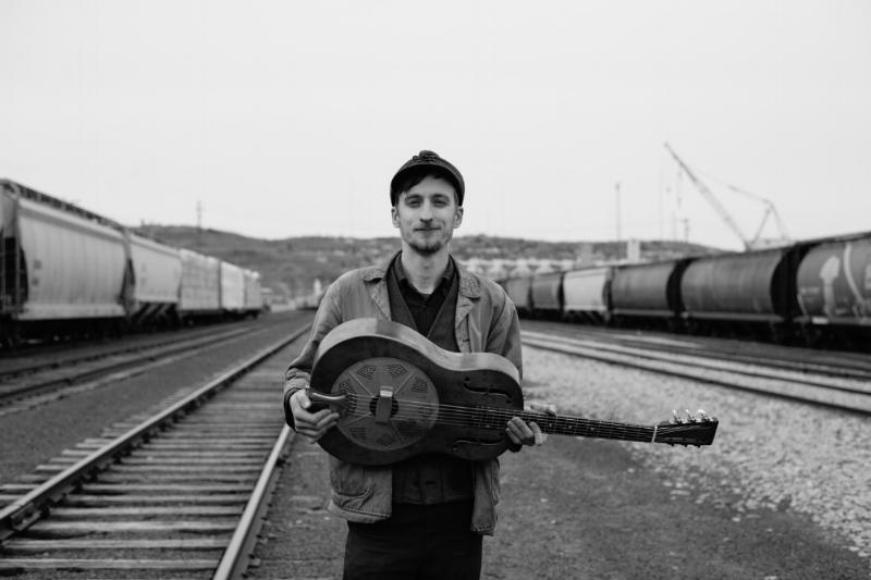Man standing in a train yard holding a resonator guitar