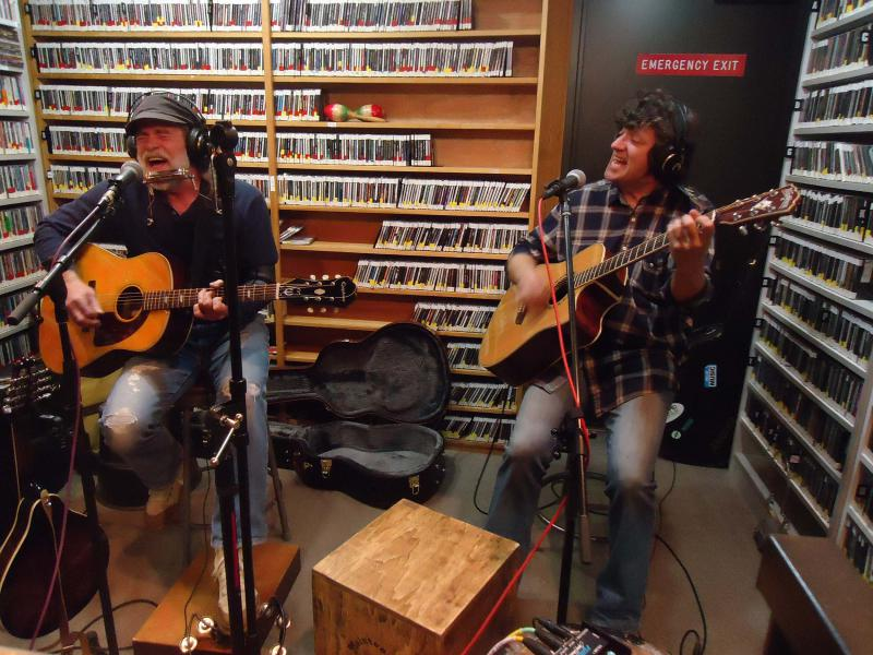 Two men playing guitar and singing in a radio studio