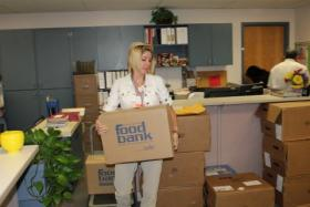 A staffer at the Garden City Unified School District 457 helps unload the weekly shipment from the Kansas Food Bank.