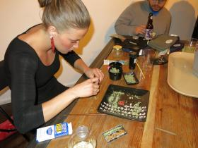 """""""Budtender"""" Rachel Schaefer shows attendees of a Denver """"bring your own cannabis"""" party how to roll marijuana into cigar papers, called blunts."""