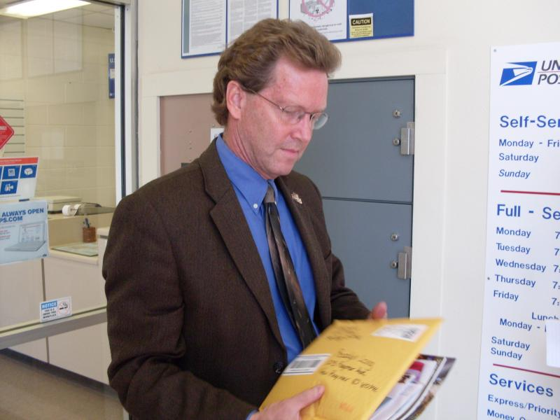 Weld County Commissioner Dave Long checks his mail at the New Raymer Post Office