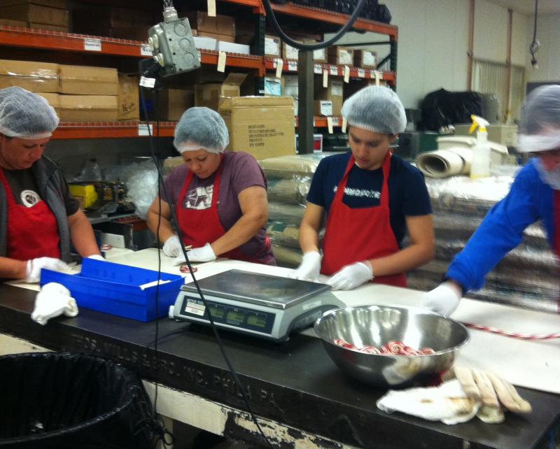 Factory workers at Hammond's Candies cut and shape candy canes on the factory floor.