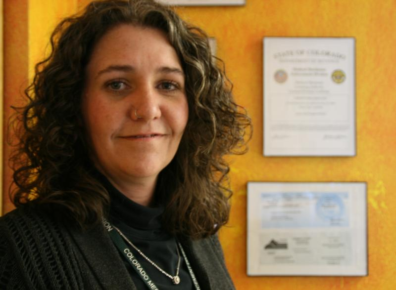 """Erica Freeman of Choice Organics stands in front of state and local business licenses. """"Those people that 280E was written for didn't have a license hanging on their wall from the state of Colorado that says you are legal to do business."""""""