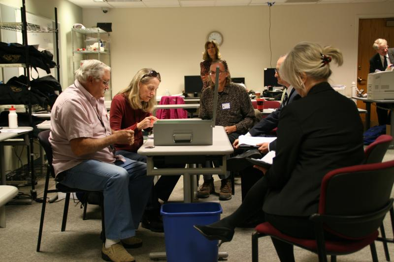 Broomfield election officials (left) worked to finalize initial election results in November before an automatic recount was triggered. To the right, several election observers look on as votes are counted.