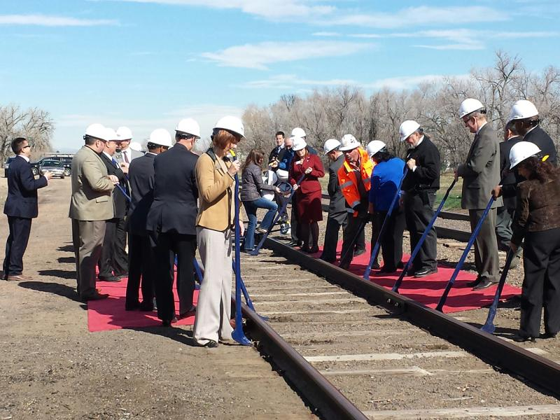 """RTD officals and local leaders peform a ceremonial """"spike-pull"""" commemorating the groundbreaking for the North Metro Rail Line."""