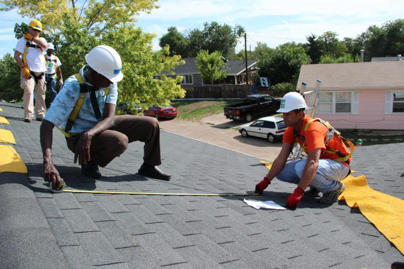 Volunteers Ken Weisbrod, right, and Abdourazak Yonis measure a roof for a Grid Alternatives solar installation.