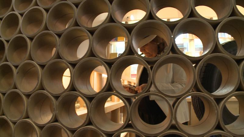A patron browses at the Aspen Art Museum's gift shop. A section of its wall consists of cardboard tubing.