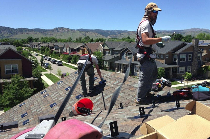 Employees with Namaste Solar install mounting brackets for a new rooftop system in Boulder, Colo.