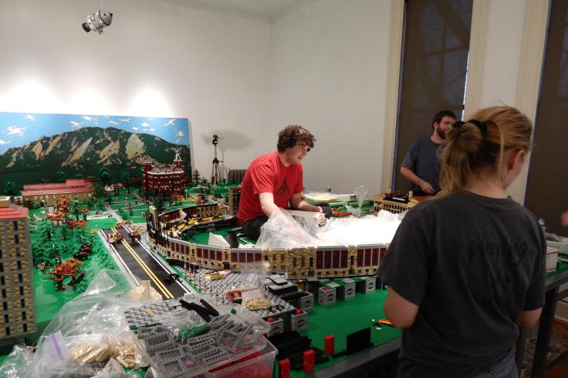 Steel folding tables were installed to hold the display's 1,000 pounds of Lego bricks and builders, like Imagine Rigney, as they work.