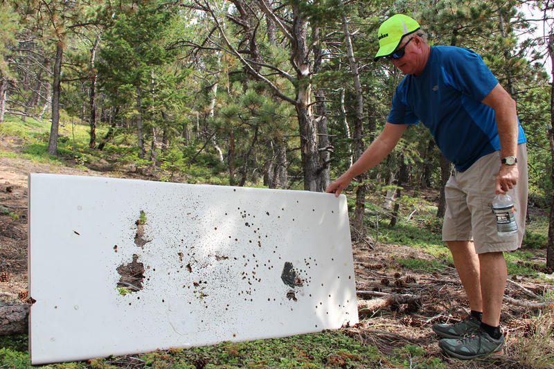John Mahoney displays a piece of countertop used for target practice and left in the forest about a mile from his home and many other homes in the Sugarloaf Mountain area of Boulder County.