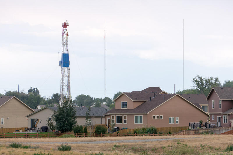 A drill rig operates between two neighborhoods in Frederick, Colo., pictured here in August 2013.