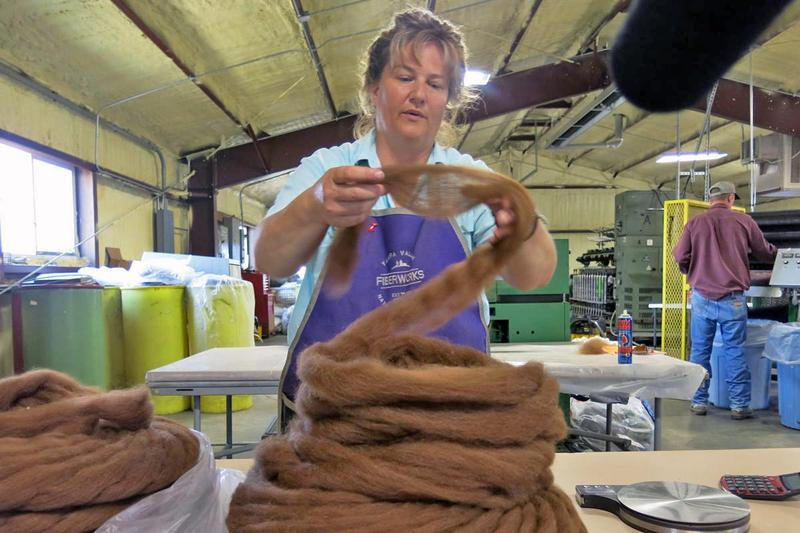 Lorrae Moon of Yampa Valley Fiberworks coils alpaca fiber into a neat stack.
