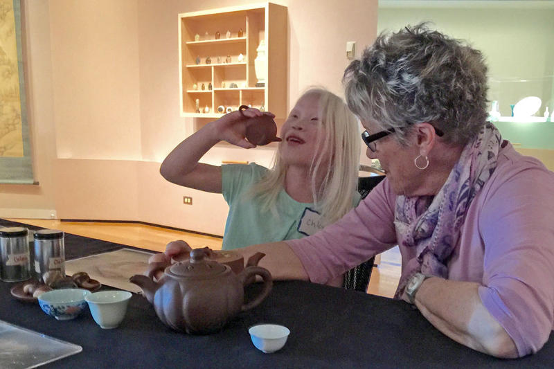 Chloe Poston plays with a replica teapot from the Denver Art Museum's Tactile Tables program.