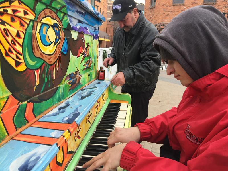 Musician Del Hayes plays the piano in Old Town Square Fort Collins while tuner Bob Otterman preps replacement keytops.