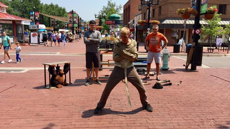 Street performer Casey Moore gets some help from the audience to lock himself into a straight jacket.