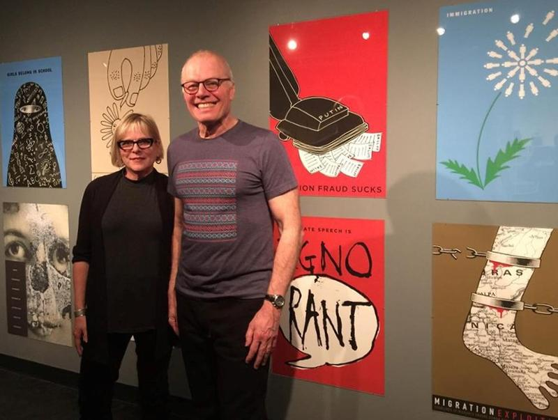 Graphic artists Alice Drueding and Joe Scorsone stand in front of part of their show as part of the Colorado International Invitational Poster Exhibition.