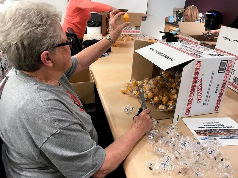 Volunteer Kay Saelens holds up a freshly unwrapped fortune cookie.