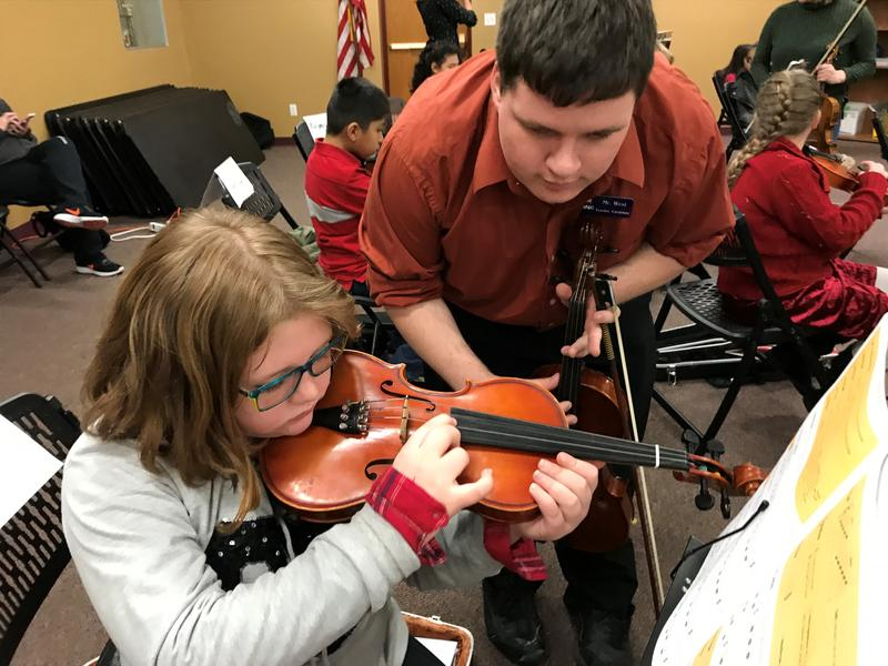 Jonathan West works with student during a UNC String Project music class.