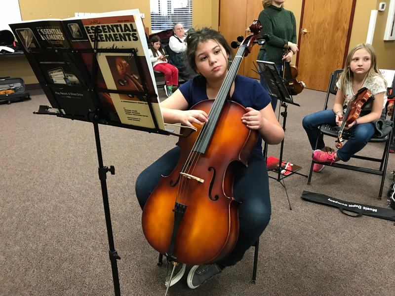 Student plays cello during UNC String Project music class.