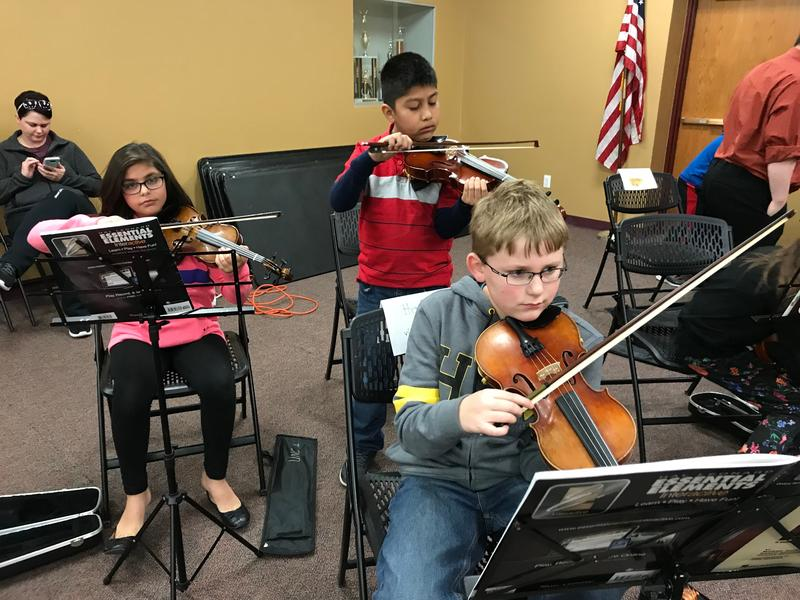 Students learn how to play string instruments during UNC String Project.