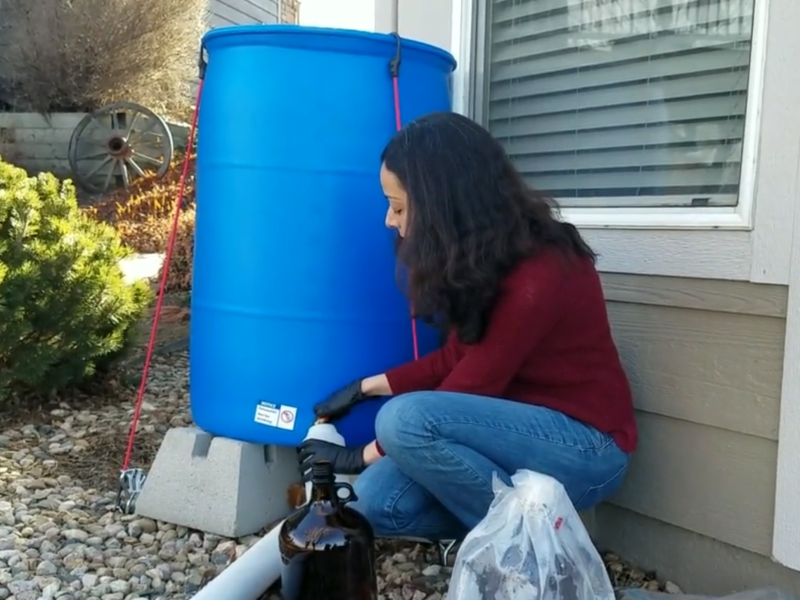 Jumana  Alja'fari, a graduate student at Colorado State University, collects a sample of rainwater from a home in Fort Collins, Colo.