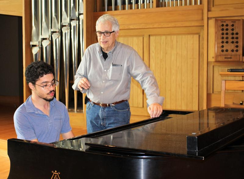 "Dr. Ed Siegel (standing) sings ""The Star-Spangled Banner"" as Ethan Boxley plays the piano."