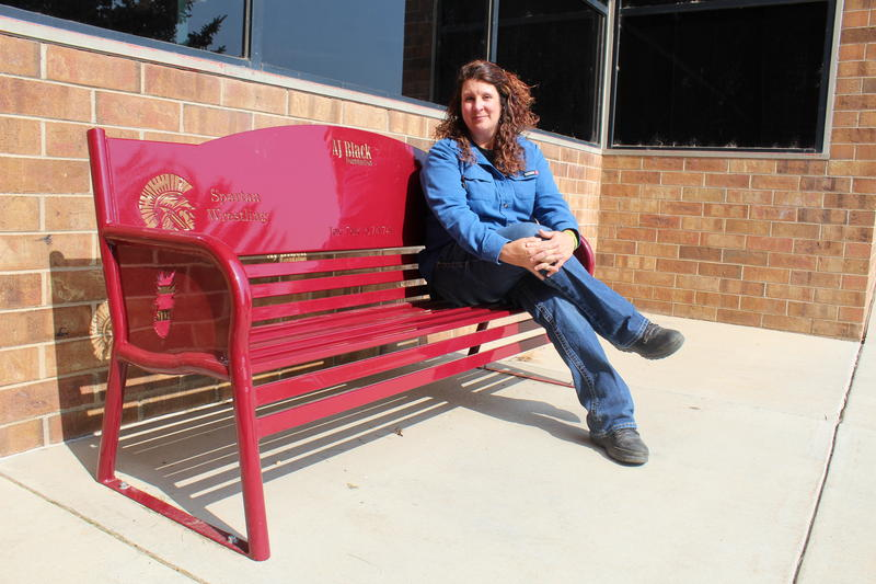 Shay Black sits on her son's memorial bench outside of Berthoud High School in Berthoud, Colorado. After AJ took his life in 2016, Shay founded a nonprofit to help other families get through their grief.