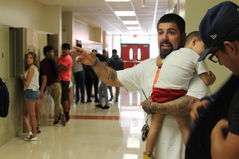 Shannon Hawley, 40, carries his son Peyton as he directs extras on the set of his new suicide prevention PSA in Milliken. Hawley started a suicide awareness organization called Hope4_2morrow earlier this year after reading about suicides in his community.