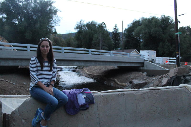 Tara Schoedinger sits in front of the Lower Main Street Bridge in Jamestown, Colo. Schoedinger is the town's flood recovery manager and was mayor during the September 2013 floods.