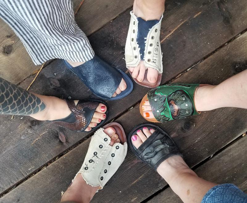 Colorado Shoe School students show off the final results of a one-day slide class. The school teaches people to make their own shoes using repurposed materials.
