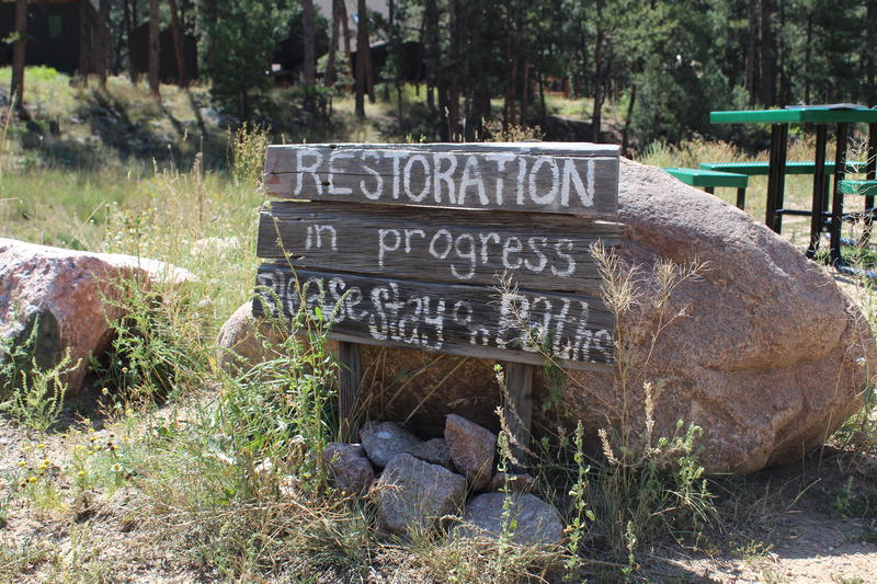 A sign reminds visitors that replanting and restoration of the area is still going on
