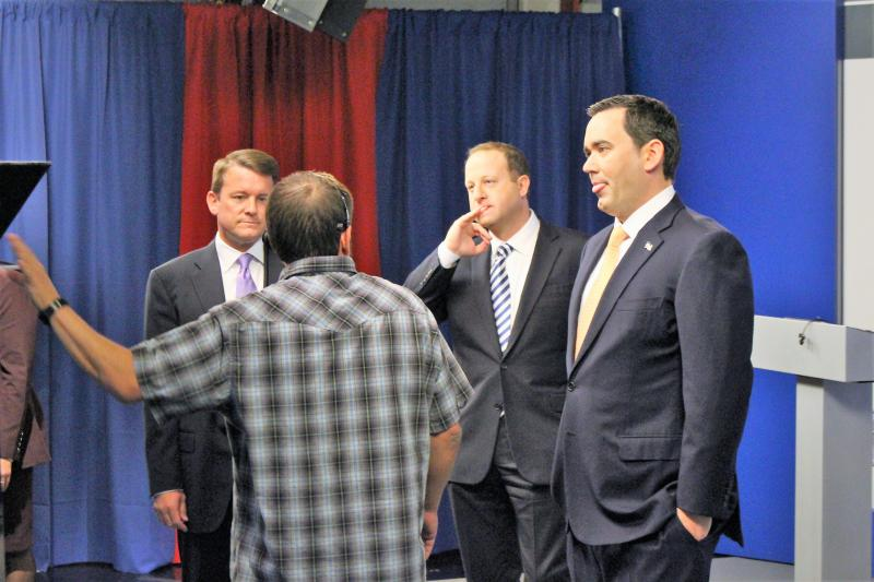 Jared Polis and Walker Stapleton prepare to take the podium Friday at a debate in downtown Denver.