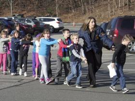 n this photo provided by the Newtown Bee, Connecticut State Police lead children from the Sandy Hook Elementary School in Newtown, Conn., following a shooting there Friday.