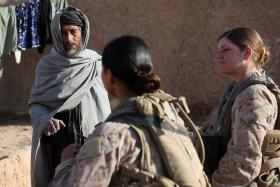 U.S. Marine Corps Sgt. Jessica Domingo, right, and Cpl. Daisy Romero, assigned to a female engagement team, speak with an Afghan man in his compound during a patrol in Marjah, Helmand province, Afghanistan, Dec. 30, 2010. The FET worked with infantry Marines by engaging women and children in support of the International Security Assistance Force.