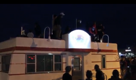 Protesters climb atop the police substation in Albuquerque's Nob Hill.