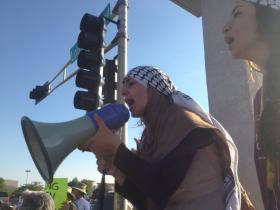 Protesting violence in Gaza with a bull-horn at the corner of Menaul and Louisiana in Albuquerque on Thursday.