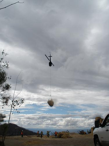 An outbound helicopter with a net full of straw headed out for an aerial mulching run.
