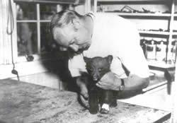 "Dr. Ed Smith and Smokey Bear in 1950.  Briefly named ""Hotfoot Teddy"" this five-pound bear with burned paws was found clinging to a charred tree during a fire in the Lincoln National Forest. He became the ""living symbol"" of Smokey Bear."