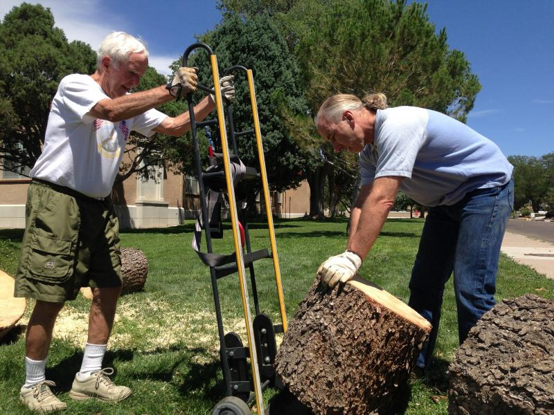 Christopher Coller helps neighbor Carl Brand (left) take pieces of firewood from an uprooted tree at Bandelier Elementary School.