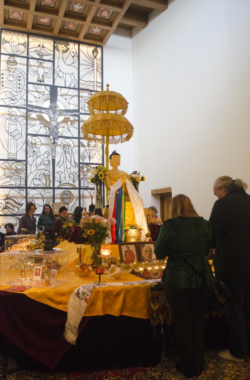 """Doug Patrick (right) and his wife Colleen McCann bathed the baby Buddha on display for purification at the exhibit on its last day in Santa Fe. """"It was pretty humbling to be around these great religious people,"""" said Patrick."""