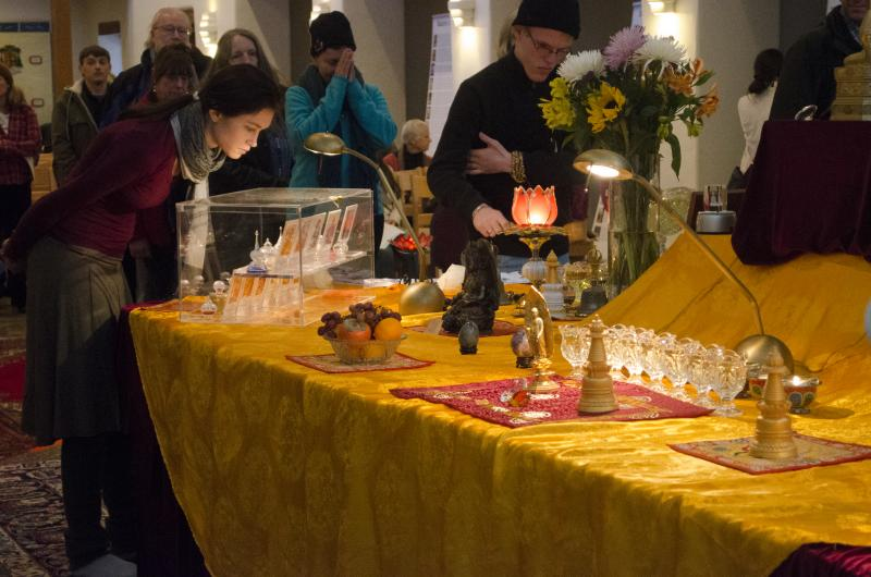 Visitors of The Maitreya Loving Kindness Tour waited in line to bathe the Baby Buddha, a practice done for purification. Four display cases around the altar displayed hundreds of ringsel for visitors to see.
